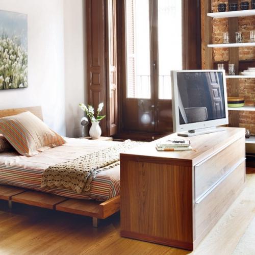 Zona de dormitor din garsoniera amenajat cu pat dublu pe mijloc