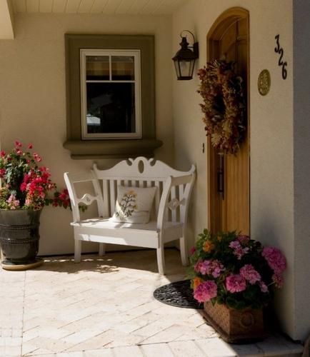 Intrare in casa decorata cu jardiniera din ratan