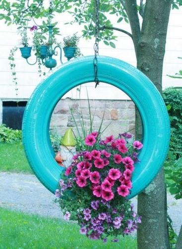 Aranjament floral pe o anvelopa bleu agatata cu lant in gradina