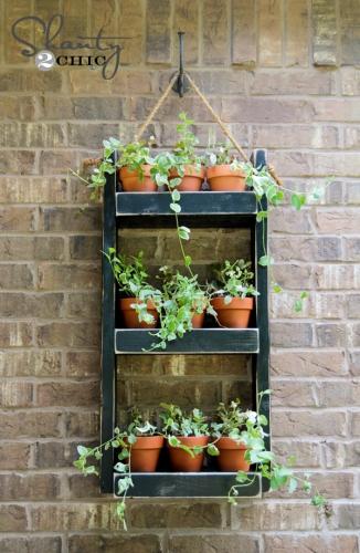 Etajere de lemn asezate pe perete cu ghivece de flori