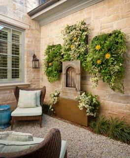 Terasa mica cu pietris si plante agatate pe zid ca un fel de gradini suspendate