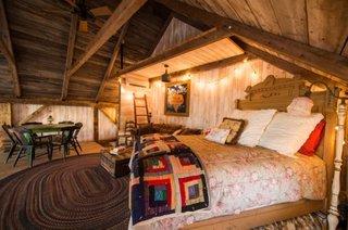 Dormitor in stil rustic amenajat in hambarul din lemn renovat