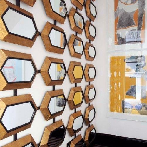 Colectie de oglinzi asezata pe peretele alb al unui hol ingust