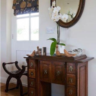 Hol amenajat in stil clasic cu masuta pentru hol veche din lemn masiv si oglinda rotunda cu rama gro