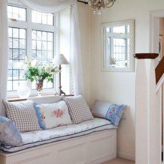 Hol cu canapea de doua locuir alba cu perne colorate decorative