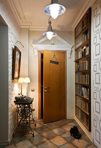 Hol de apartament decorat la intrare cu masuta de hol retro din fier forjat si biblioteca