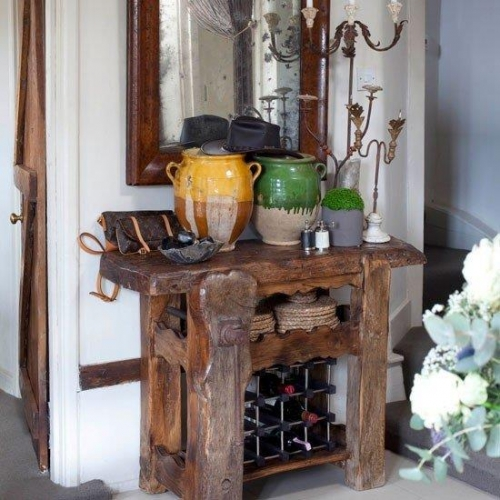 Masuta cu suport pentru vinuri asezata intr-un hol micut rustic