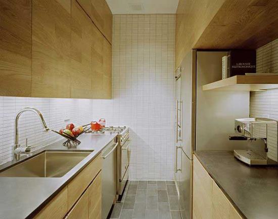 Bucatarie dintr-un mic apartament cu dulapuri din lemn natur