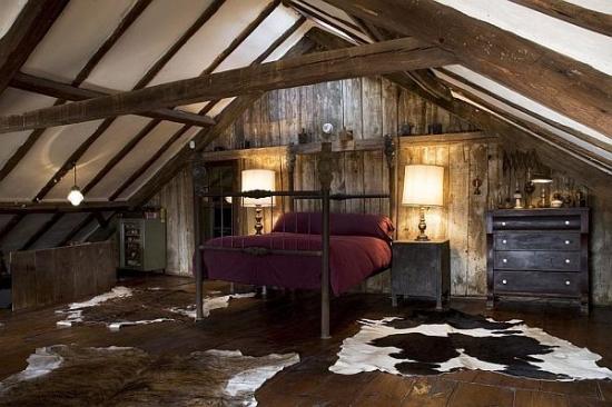 Dormitor mare amenajat in mansarda in stil rustic cu covoare din piele