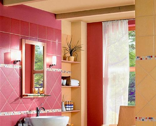 Baie cu pereti roz si portocalii si rafturi suspendate pe pereti