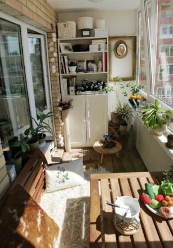 Amenajarea unui balcon inchis de apartament cu masa mica din lemn si un dulapior