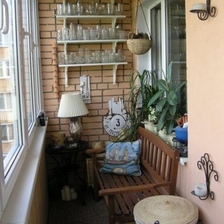 Banca de lemn si masuta mica asezate in balcon cu perete din caramida