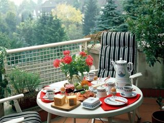Masuta mica rotunda si doua fotolii comode asezate in balcon