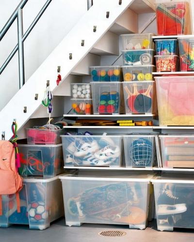 Cutii din plastic asezate una peste alta si depozitate sub scara