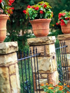 Gard cu stalpi placati cu piatra decorativa si zabrele din fier forjat