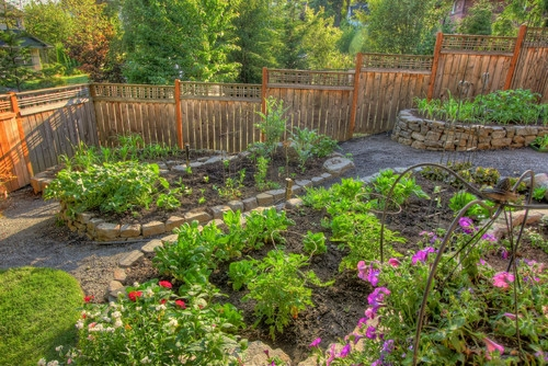 Idee pentru decorarea si aranjarea unei gradini de flori cu ronduri din pietre si gard de lemn