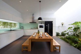 Bucatarie cu mobila alba si masa lunga din lemn cu bancute si gradina interioara