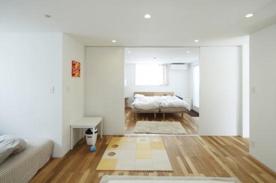 Interior de dormitor in stil japonez cu pereti albi si mobila putina