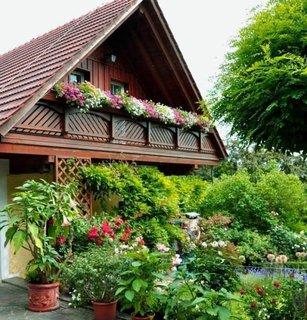 Casa cu masarda din lemn si muscate curgatoare albe si roz