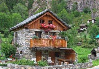 Casa rustica din piatra si lemn cu muscate la balcon
