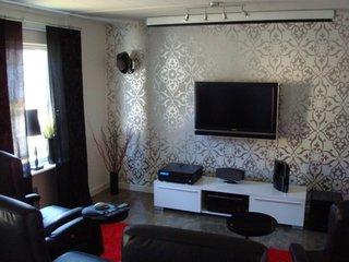 Living mic cu perete cu tapet gri cu argintiu si televizor montat pe perete