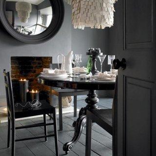 Loc de servit masa cu peretii si parchetul albe si masa si scaune negre