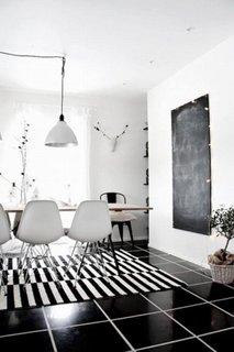 Zona de dining cu pardoseala neagra si traverse tesute in dungi
