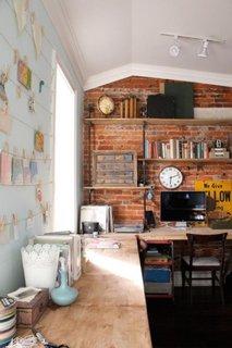 Decor camera de studiu cu perete din caramida nefinisata