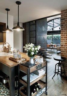 Loft industrial amenajat cu caramida fier negru si lemn inchis la culoare