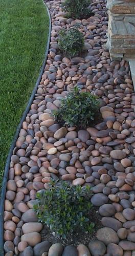 Rond de flori cu pietre rotunde combinat cu gazon