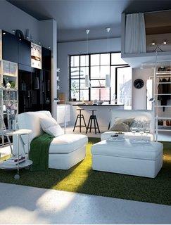 Garsoniera amenajata cu canapea mica alba si covor verde si pat etajat