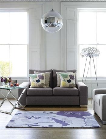 Living simplu gri cu canapea cu doua locuri si covor alb cu mov inchis