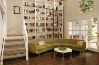 Rafturi inalte cu scara de lemn si canapea olive