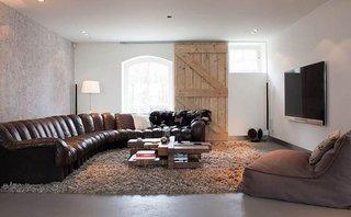 Canapea de piele maro pe curb si usa din lemn culisanta