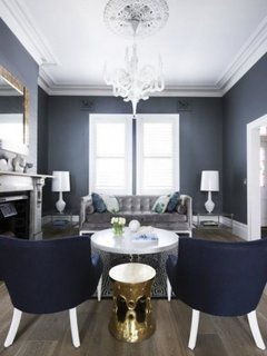 Pereti gri albastrui  scaune albastre si candelabru clasic in living