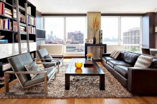 Sufragerie cu canapea maro de piele covor pufos masuta de lemn biblioteca