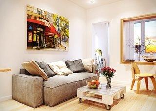 Living de mici dimensiuni cu canapea gri si pictura deasupra foarte colorata