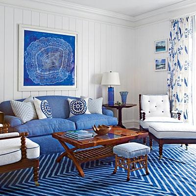Canapea albastru intens asortata cu tablou si covor