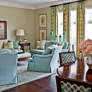 Fotolii si canapea bleu si parchet din lemn inchis la culoare si draperii galbene