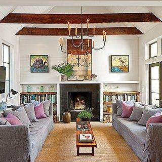 Living cu doua canapele asezate fata in fata si barne din lemn pe tavan