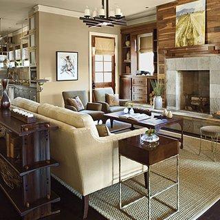 Living cu perete placat cu lemn canapea crem si covor de iuta