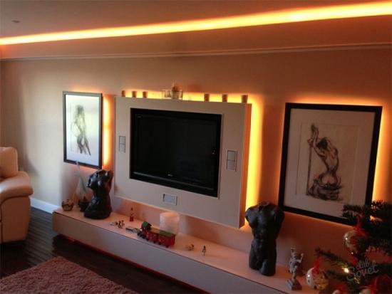 Perete cu televizor si tablouri cu lumini in spate