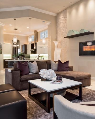 Living cu canapea pe colt de culoare gri si sistem de iluminat cu spoturi si suspensii