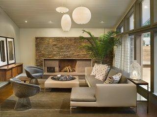 Living modern cu perete placat cu piatra si lustre albe asortate