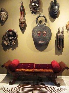 Bancuta de lemn cu pernute si masti decorative mari pe peretele de deasupra ei