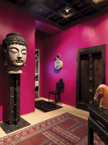 Hol de intrare vopsit in purpuriu si masca mare decorativa pe stativ