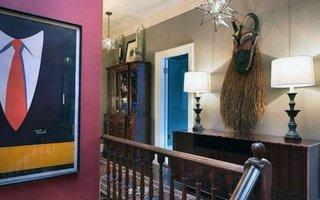 Hol interior amenajat cu mobilier maro inchis si masca africana de mari dimensiuni