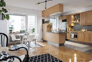 Bucatarie cu mobila din lemn si bar cu lumini suspendate