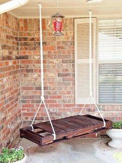 Leagan pe terasa unei case cu exterior din piatra