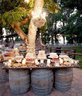 Idee pentru aranjarea mesei cu bufet suedez la o petrecere in gradina utilizand niste butoaie